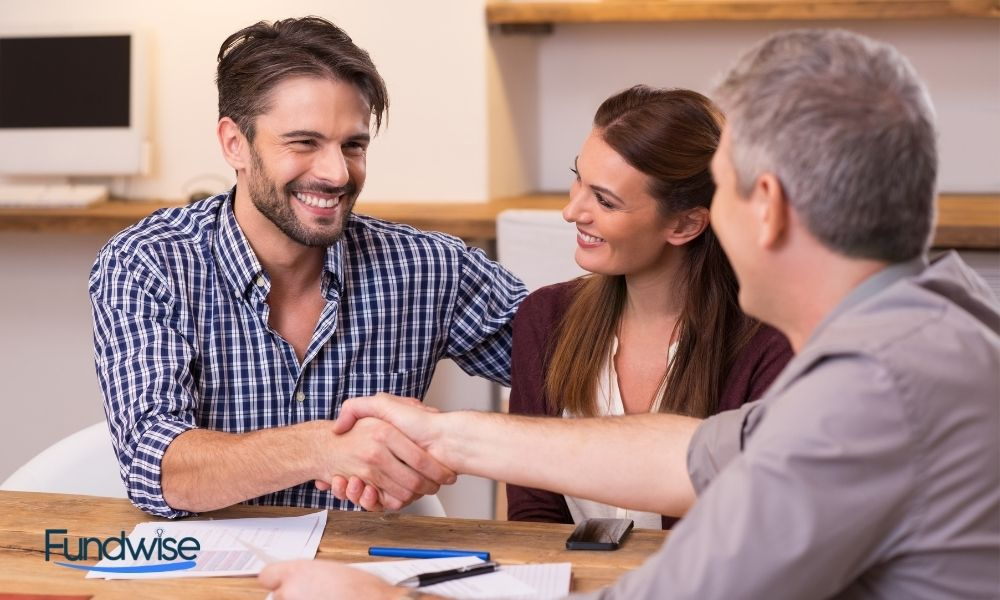 Couple shaking hand to a business financial advisor