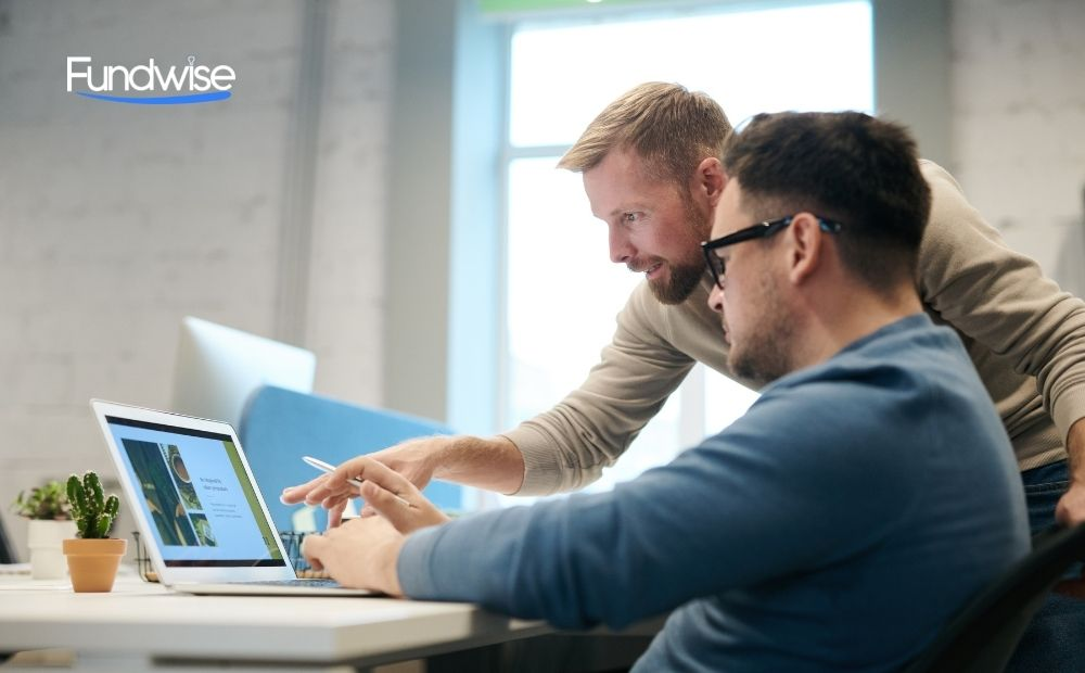 two business owners discussing in front of a laptop